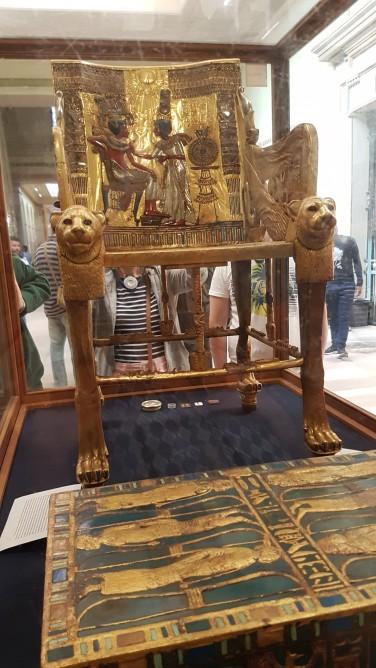 Tutankamon și soția lui protejați de razele zeului RA. Aceasta îi face masaj având în mână anfora cu uleiuri esențiale de lotus și papirus. Faptul că fiecare poartă doar un pantof simbolizează că sunt suflete pereche.