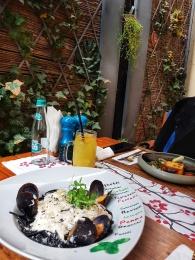 spaghetele negre cu fructe de mare, ardei iute, gălbiori și brânză neagră cu cărbune și păstrăv la cuptor cu mămăliga coaptă și infuzată în flori de tei